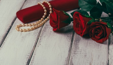 Roses and gift box with bead on wooden table. Valentines day concept. Copy space